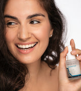 Model holding Vasanti Brighten Up! Glow Boosting Serum