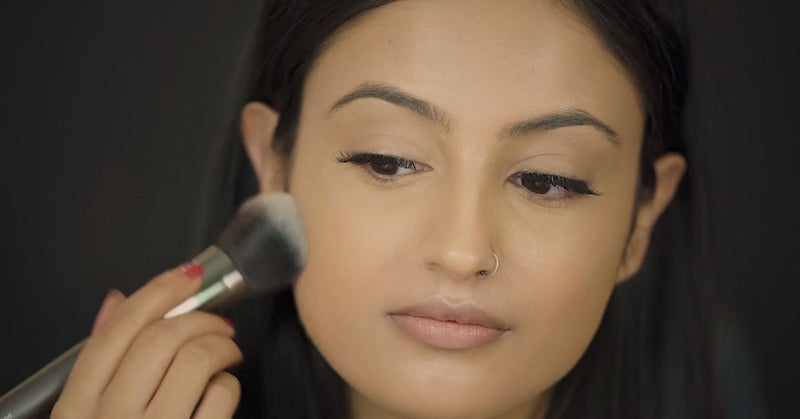 Woman applying Vasanti Face Base Powder Foundation on her cheeks - on black background