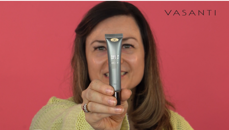 A woman holding Vasanti Liquid Cover Up Foundation and Concealer in 1 on pink background.
