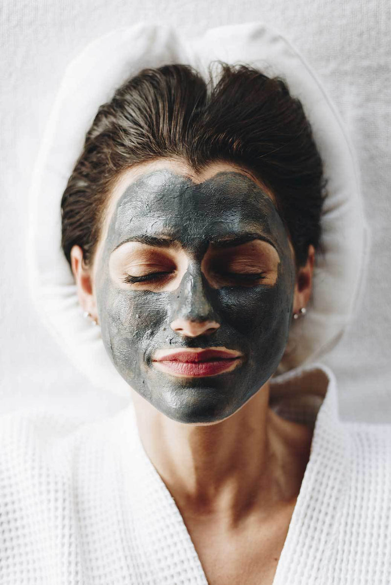 A woman lying down, face covered in Vasanti Brighten Up! Miracle Mask