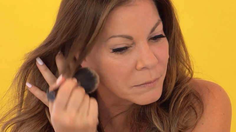 Woman applying Vasanti Face Base Powder Foundation on her cheeks - on yellow background