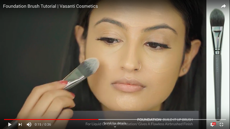 A girl applying foundation to her face using Vasanti Foundation Build it Up Brush - Screenshot from Youtube video.