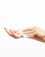 A hand holding a piece of Vasanti Makeup Magnet Wipes