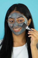 A girl applying Vasanti Brighten Up! Miracle Mask on her face using Vasanti Stubby Miracle Mask Brush