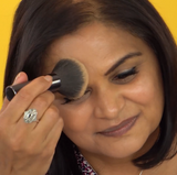 Woman using Vasanti Stubby Powder Brush on her face to apply makeup.