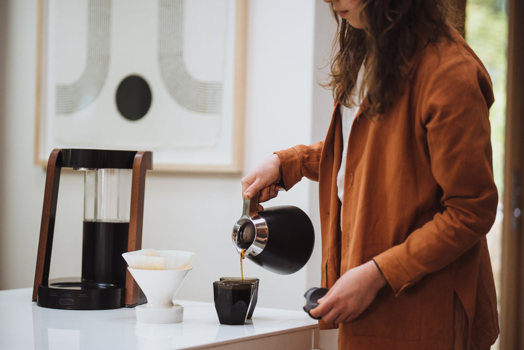 A woman pours coffee from a Ratio Eight thermal carafe into a glass.