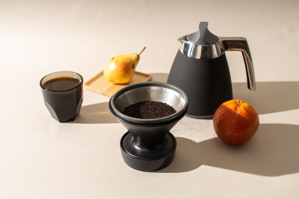 An Able Kone metal coffee filter in a Ratio ceramic dripper, next to a Ratio Thermal Carafe in matte black.