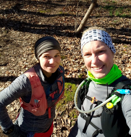 Two white women dressed for trail running on a leaf covered trail, wearing Ponya Bands.