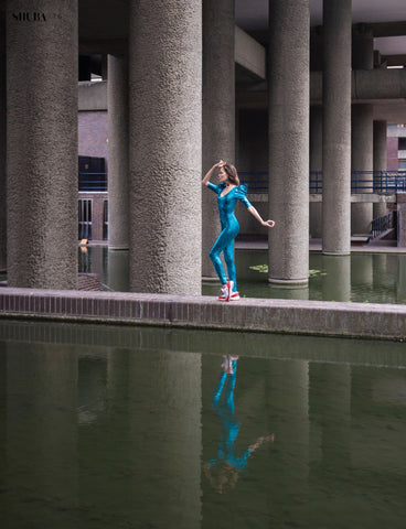 model wearing turquoise catsuit at barbican centre london