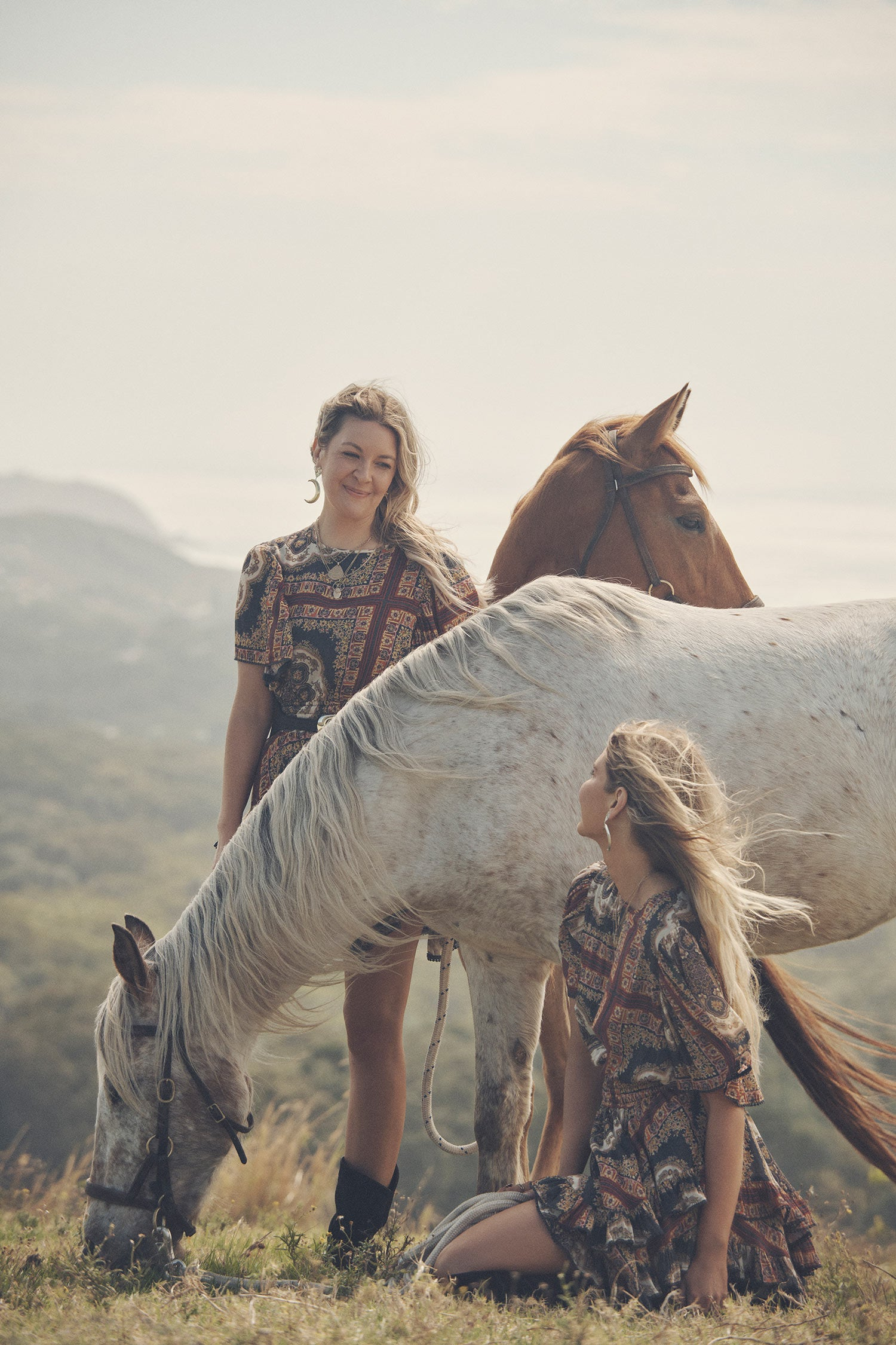 Sisters, Lucie and Elle Ferguson, posing in a green pasture with horses while wearing gold jewellery, black boots and the Spell regal Rumour Print Mini Dress with flutter sleeves and a gathered frill hem.
