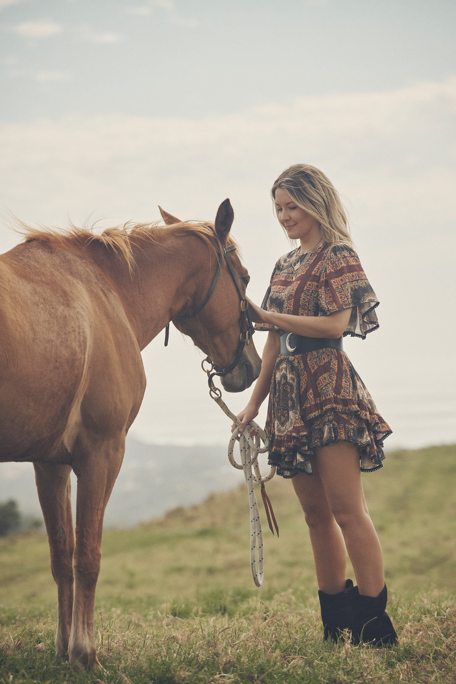 Jeweller and campaign model, Lucie Ferguson, posing in a green pasture with horses while wearing gold jewellery, black boots and the Spell regal Rumour Print Mini Dress with flutter sleeves and a gathered frill hem.