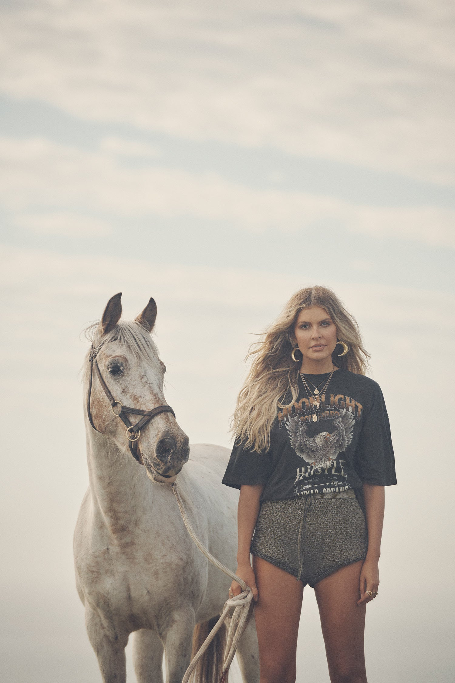 Influencer and model, Elle Ferguson, standing next to a white horse while wearing gold necklaces, the Spell Lucy Luna Earrings, oxyn Moonlight Shorts and the oversized biker charcoal Cult Tee Dress.