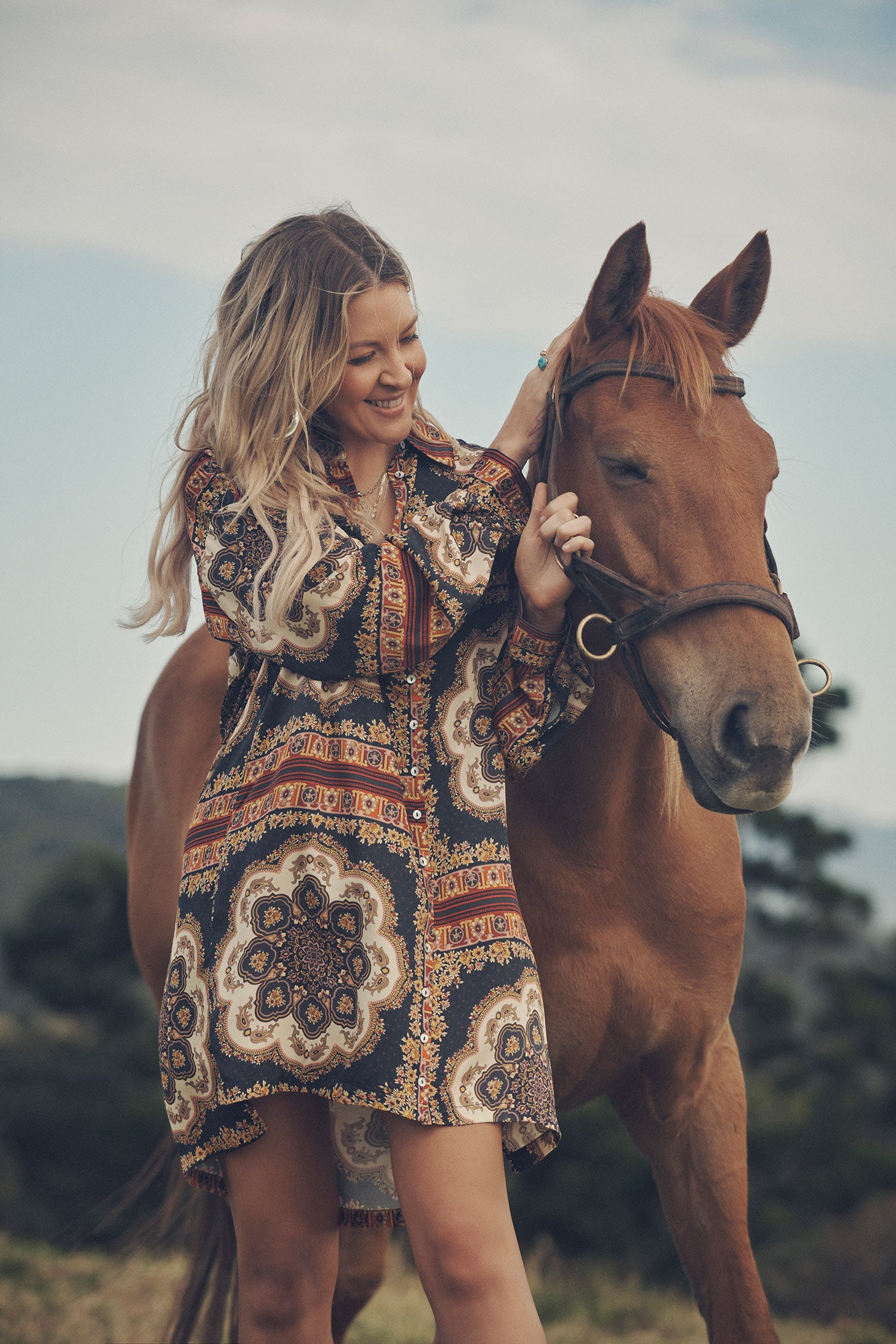 SpellJeweller and campaign model, Lucie Ferguson, posing in a green pasture with a brown horse while wearing gold jewellery, the Spell Cult Suede Slouch Boots and the Spell regal Rumour Print Shirt Dress.
