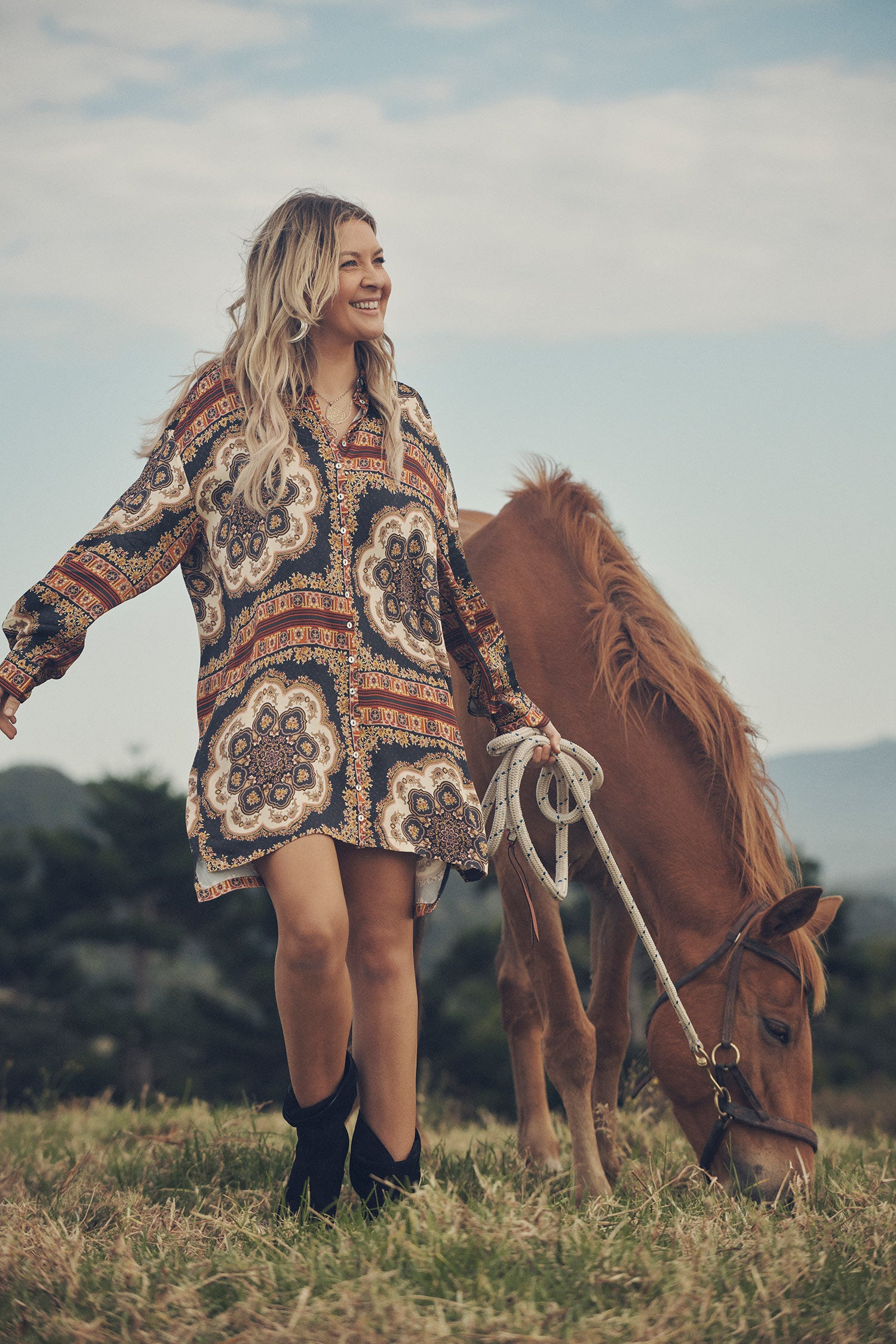Jeweller and campaign model, Lucie Ferguson, posing in a green pasture with a brown horse while wearing gold jewellery, the Spell Cult Suede Slouch Boots and the Spell regal Rumour Print Shirt Dress.