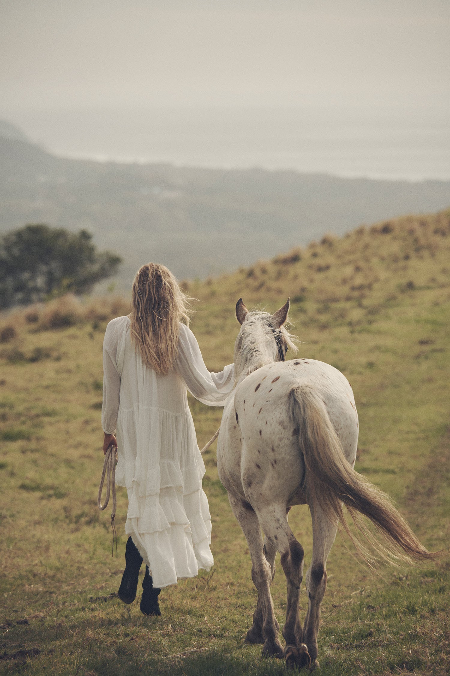 Influencer and model, Elle Ferguson, posing in a green pasture with a white horse while wearing gold jewellery, the Spell Cult Suede Slouch Boots with the white, tiered Moonflower Gown featuring frills and elasticated cuffs.