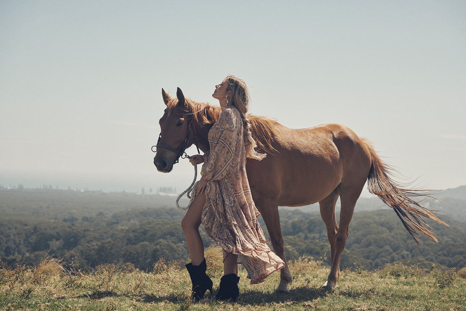 Jeweller and campaign model, Lucie Ferguson, posing in a green pasture with a brown horse while wearing gold jewellery, the Spell Cult Suede Slouch Boots with the pale pink, tiered Rumour Print Elle Gown featuring frills and elasticated cuffs.