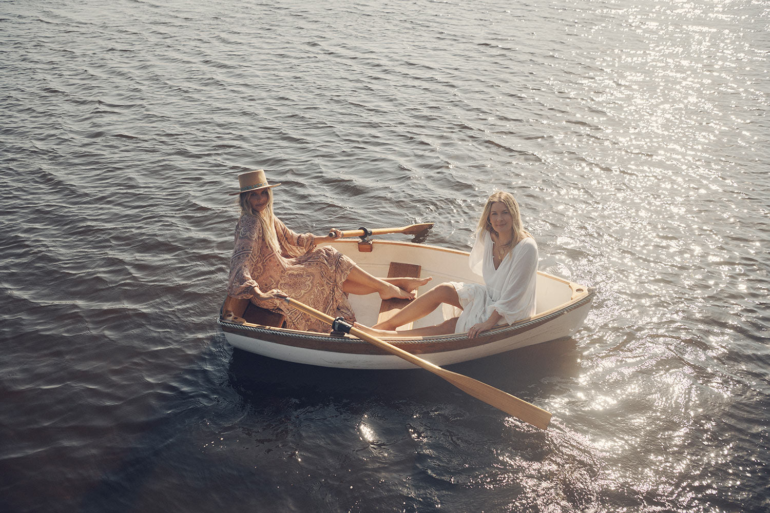 Sisters, Lucie and Elle Ferguson, on a white rowboat in the middle of a river wearing the white tiered Spell Moonflower Gown and the pale pink Spell Rumour Print Elle Gown, both featuring tiered skirts, ruffles and elasticated cuffs.