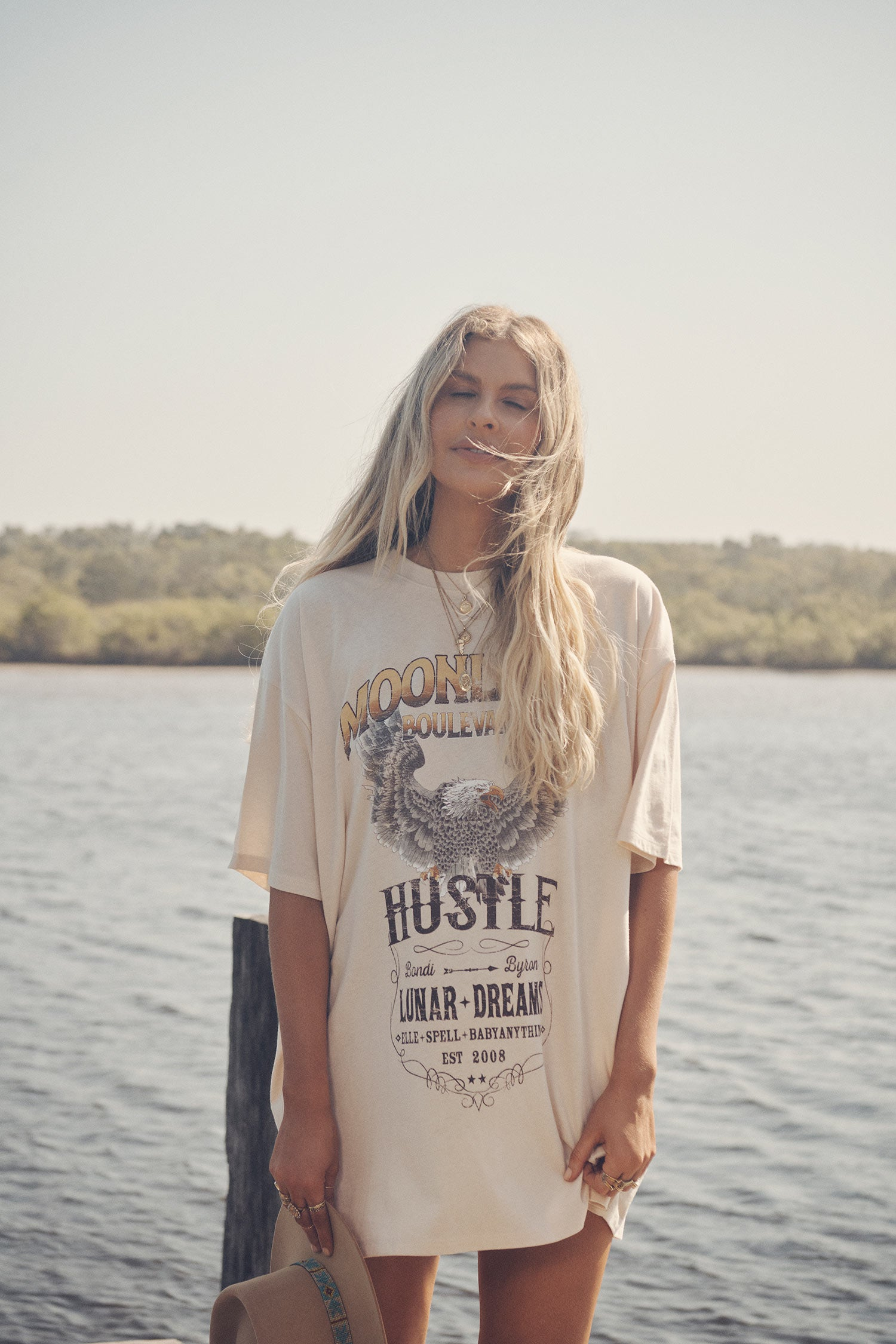 Influencer and model, Elle Ferguson, standing on a wooden dock at a river holding a camel felt hat while wearing gold jewellery and the oversized white Spell Cult Tee Dress, featuring a print on the front.