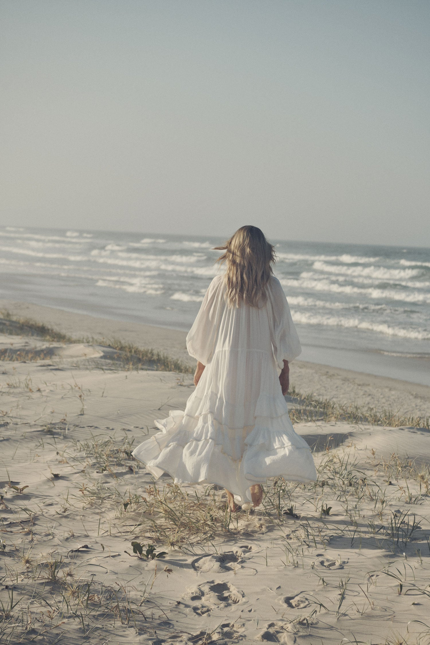 Jeweller and campaign model, Lucie Ferguson, walking on a sand dune while wearing gold jewellery and the white Spell Moonflower Gown featuring elasticated cuffs and a tiered skirt.