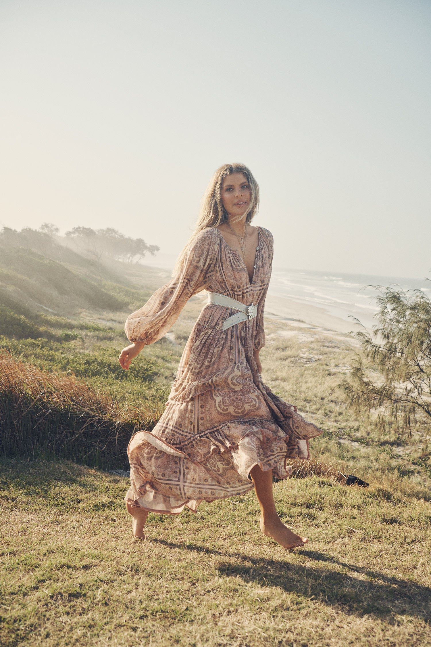 Influencer and model, Elle Ferguson, posing on a grassy hill overlooking a beach while wearing gold jewellery, a white belt and the pale pink Spell Rumour Print Elle Gown, featuring a tiered skirt, ruffles and elasticated cuffs.