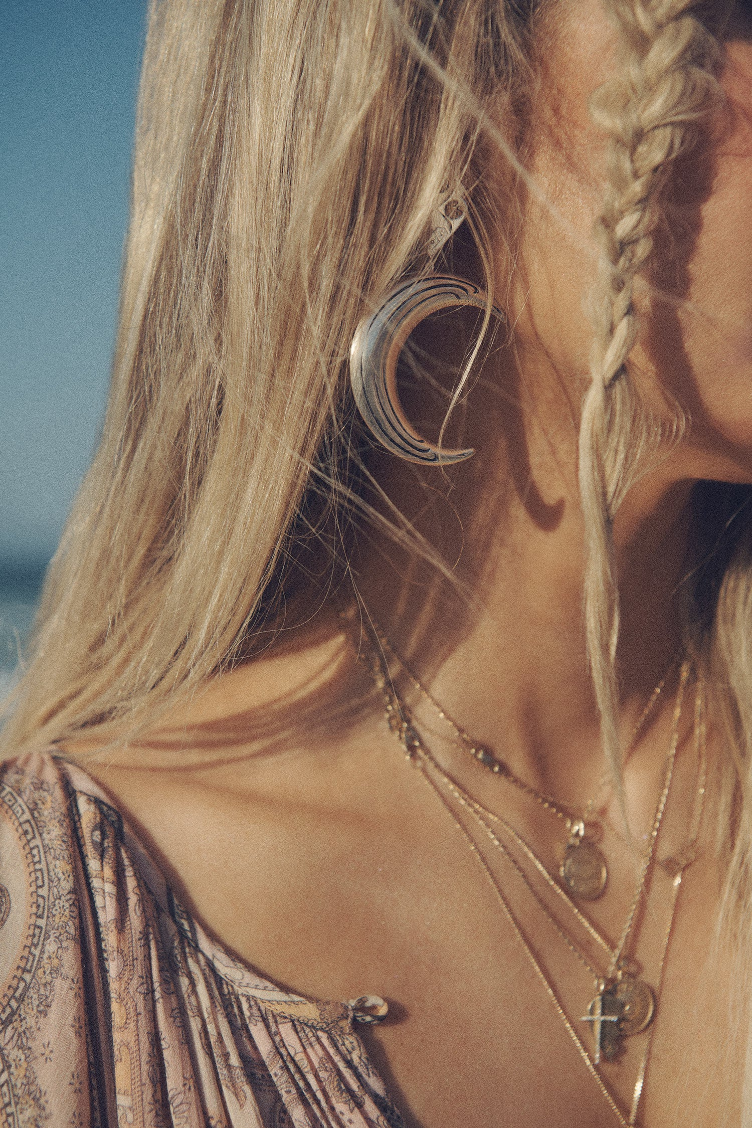 A close-up image of influencer and model, Elle Ferguson, wearing gold jewellery paired with the silver moon-shaped Lucie Luna Earrings.