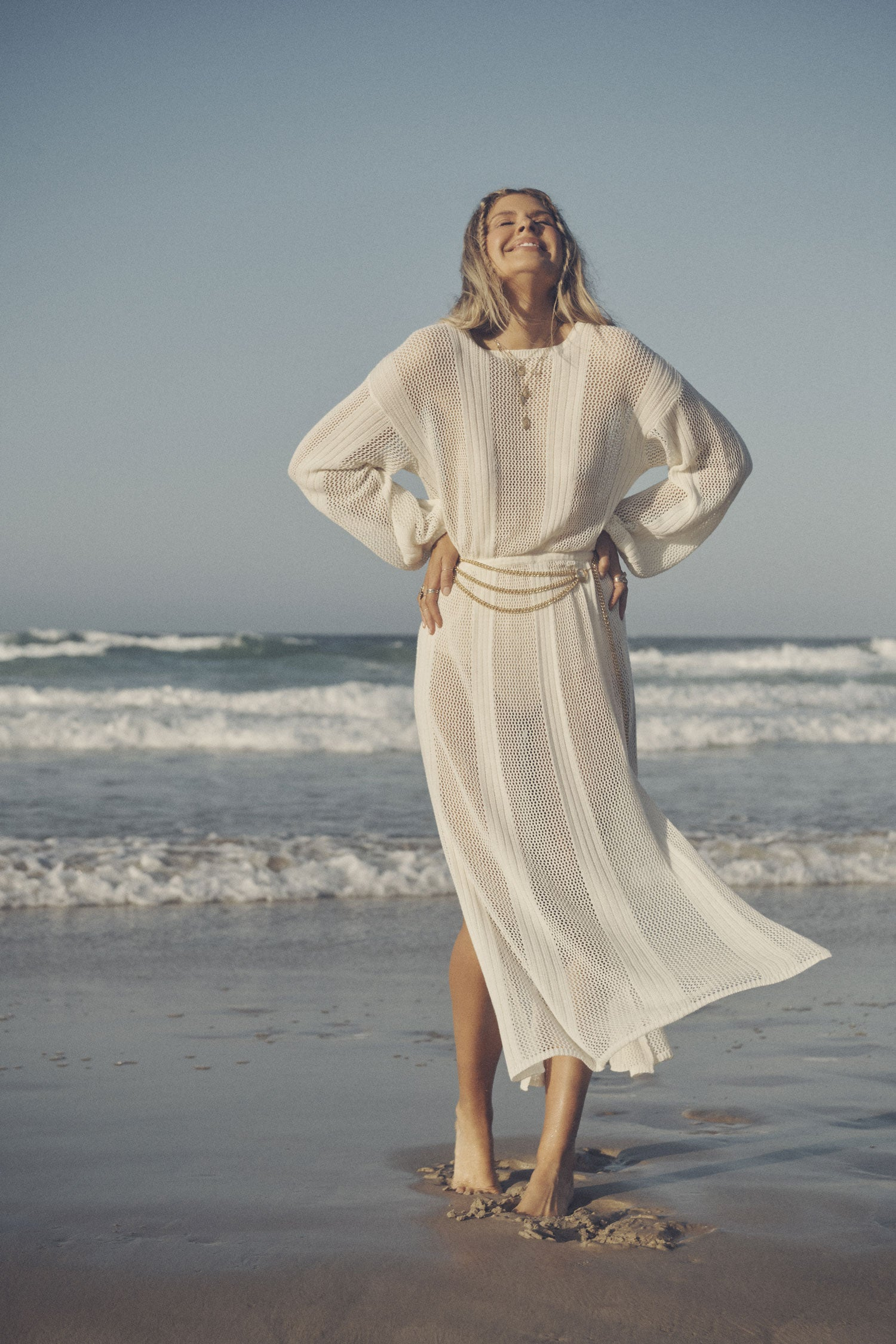 Influencer and model, Elle Ferguson, posing on a beach while wearing gold jewellery, the Spell Belladonna Chain Belt and the cream Rush Knit Midi Dress, featuring side splits and an elasticated waistline.