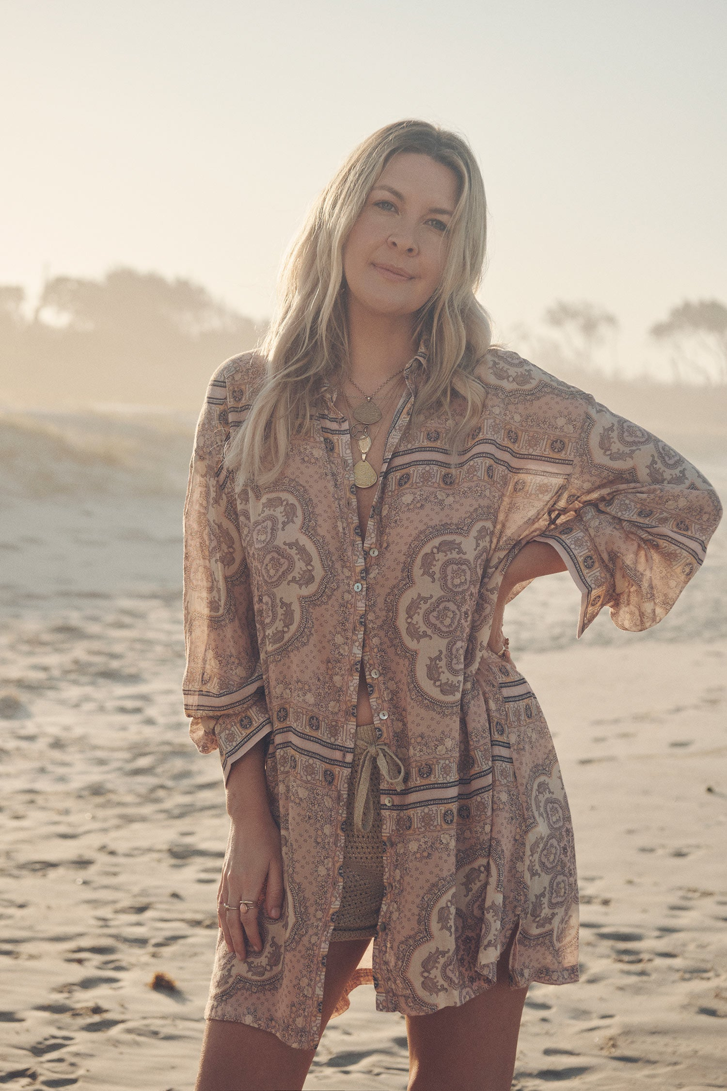 Jeweller and campaign model, Lucie Ferguson, posing on a beach while wearing gold jewellery, the golden Spell Moonlight shorts and the pale pink Spell Rumour Print Shirt Dress, featuring a shell button down front and collar.