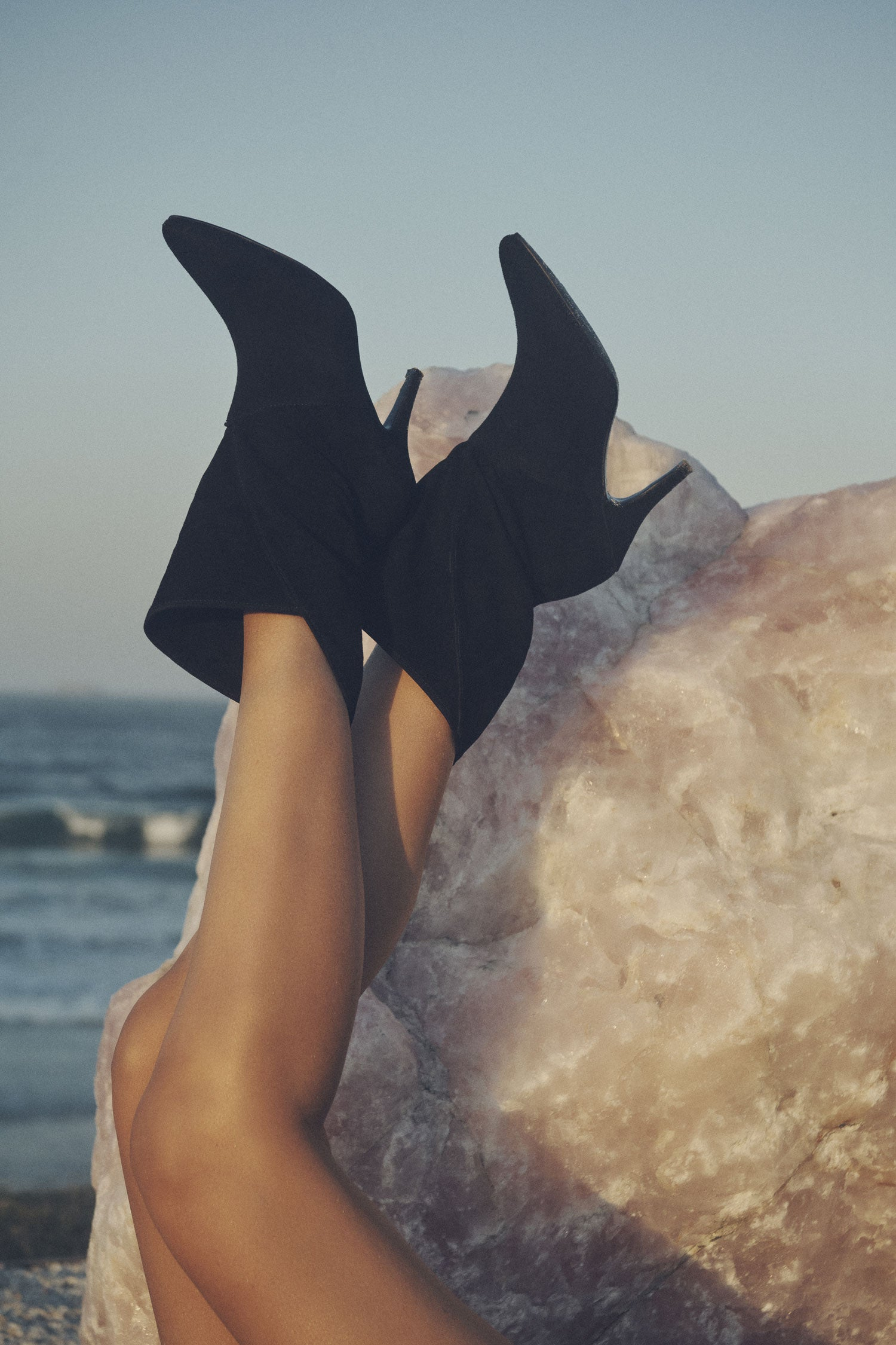 A close- up image of the Spell black Cult Suede Boots, featuring a pointed toe and narrow heel, with a crystal and beach in the background.