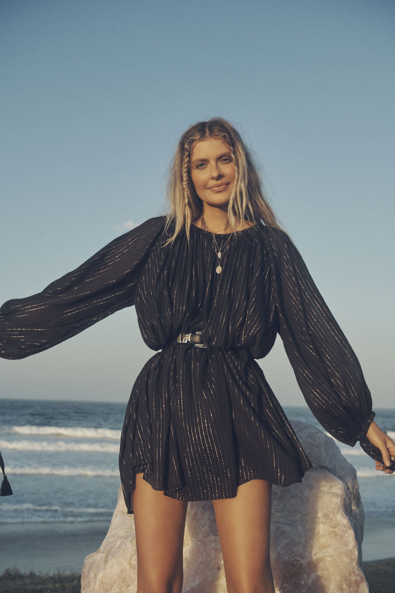 Influencer and model, Elle Ferguson, posing in front of a large crystal with the beach in the background while wearing gold jewellery, a black belt and the Spell black, metallic Jagger Mini Dress with elasticated cuffs.