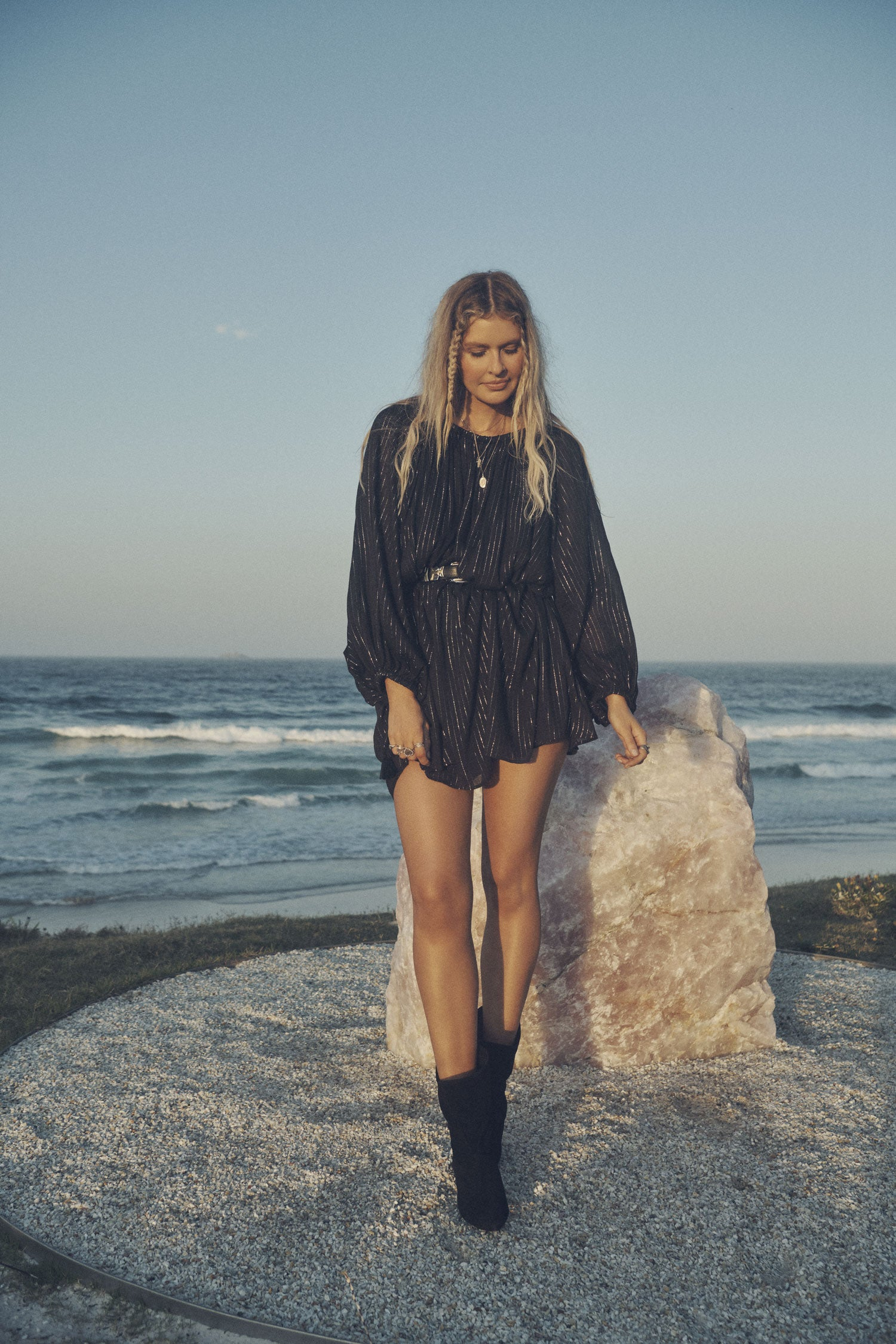 Influencer and model, Elle Ferguson, posing in front of a large crystal with the beach in the background while wearing gold jewellery, a black belt, the Spell Cult Suede Slouch Boots and the Spell black, metallic Jagger Mini Dress with elasticated cuffs.