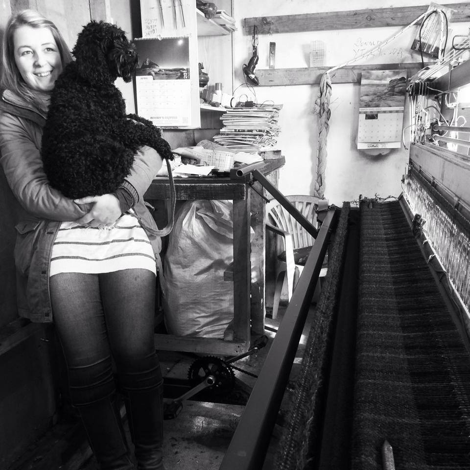 Eilidh Campbell and her dog Isla visiting a Harris Tweed loom on the Isle of Lewis