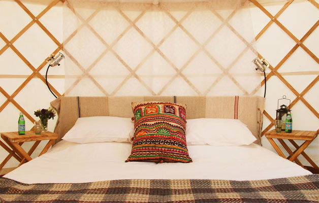 Port Eliot Luxury Yurt. King size bed with white cotton linen, duvet and pillows. Bespoke furniture.