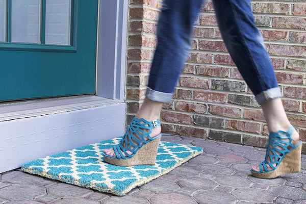 A teal doormat with a crosscross white Moroccon style print with a woman in heels walking across it.