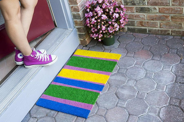 Coir doormat with yellow, blue, pink and green stripes outside door.