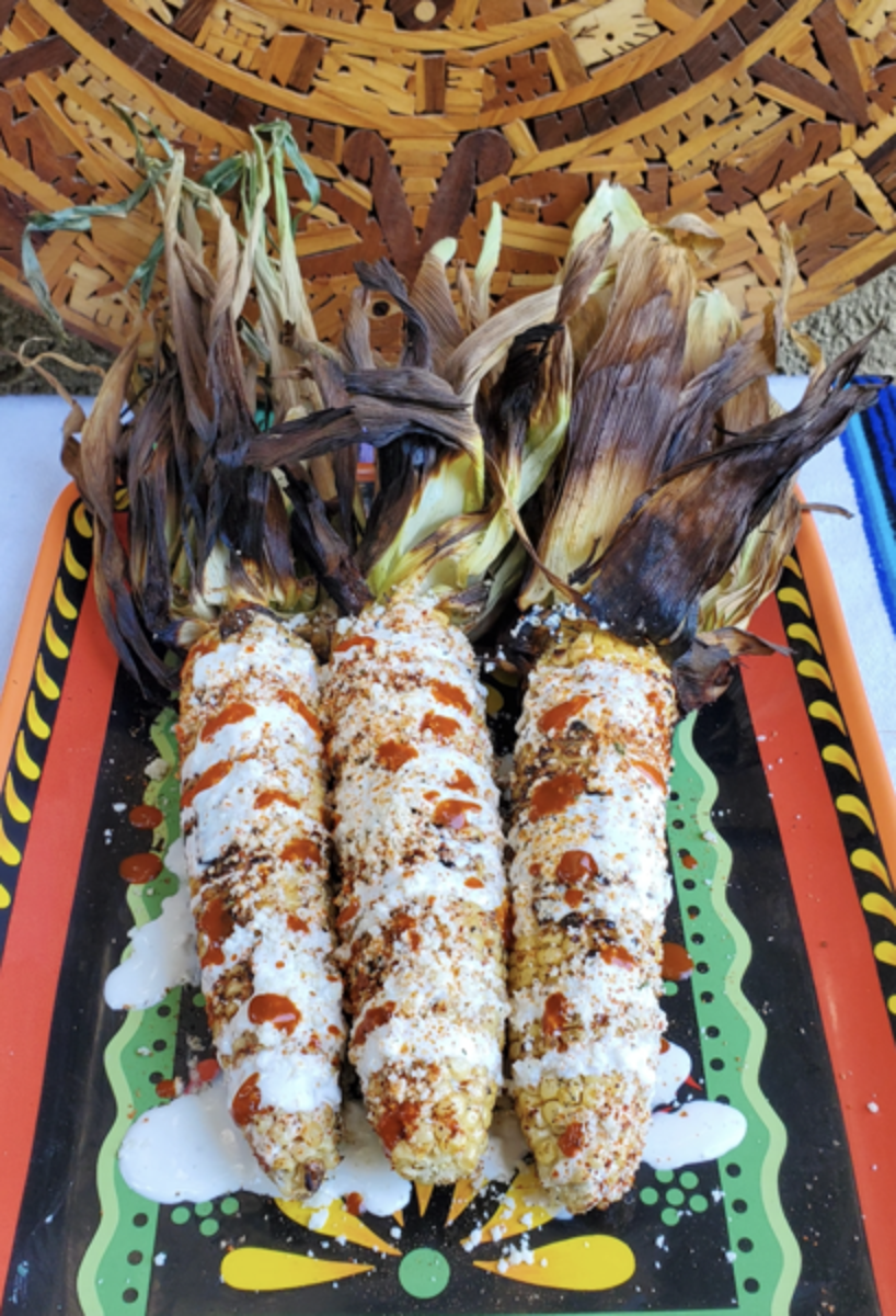 Smoked Mexican Street Corn on Festive Dish Drizzled with Hot Sauce