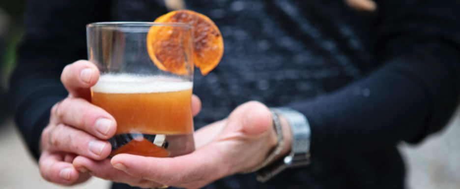 Maple Man Cocktail with Orange Slice in Hand