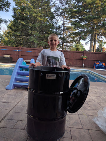 Tristan (10), helps his father Joel light the coals and load up the PBC in New-Brunswick, Canada