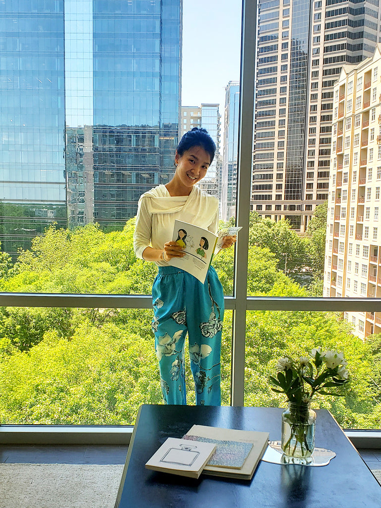 Grace Jun looks through NOT's fashion coloring book in her building with a natural window view.