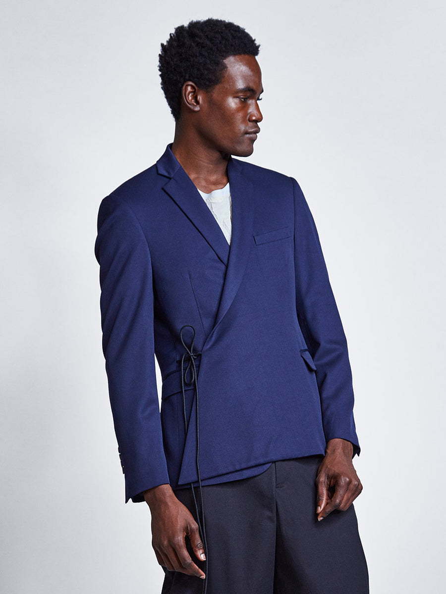 Men's navy blue tailored wrap blazer jacket with cord tie.