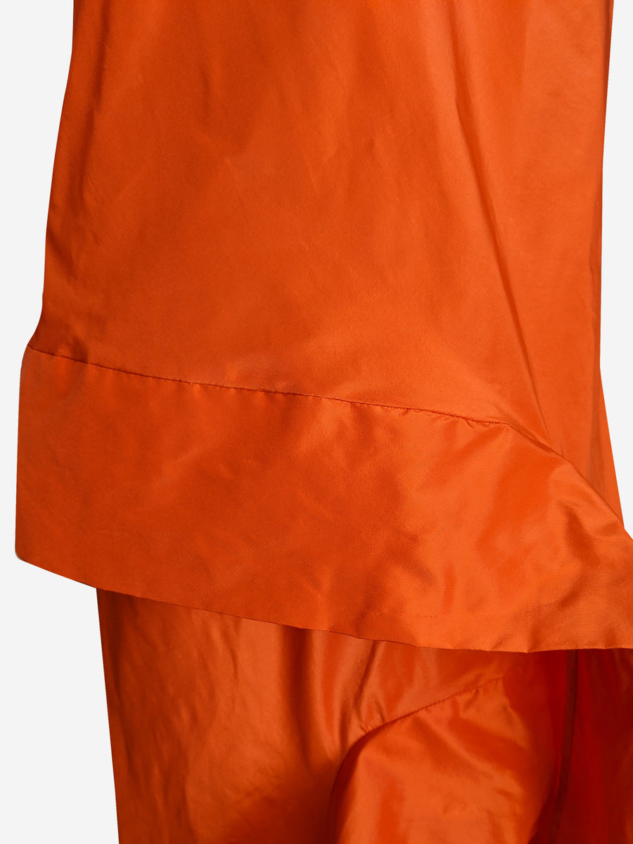 Detail of bright orange silk taffeta asymmetric long evening dress