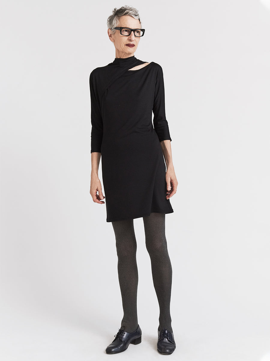 Black jersey designer dress with split dolman sleeves and mock turtleneck.