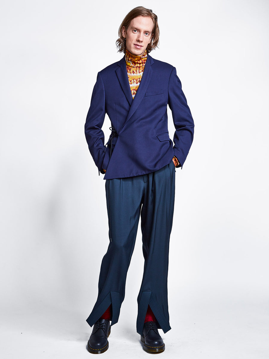 Men's navy blue tailored wrap blazer jacket with cord tie over teal pleated wide leg pants and printed turtleneck.