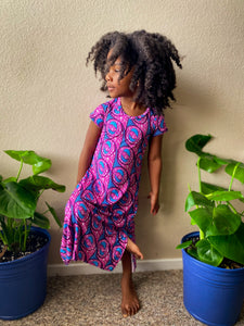 Image of Black child in pink and blue dress surrounded by plants