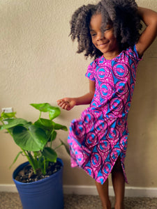 Image of Black child in pink and blue dress with a plant