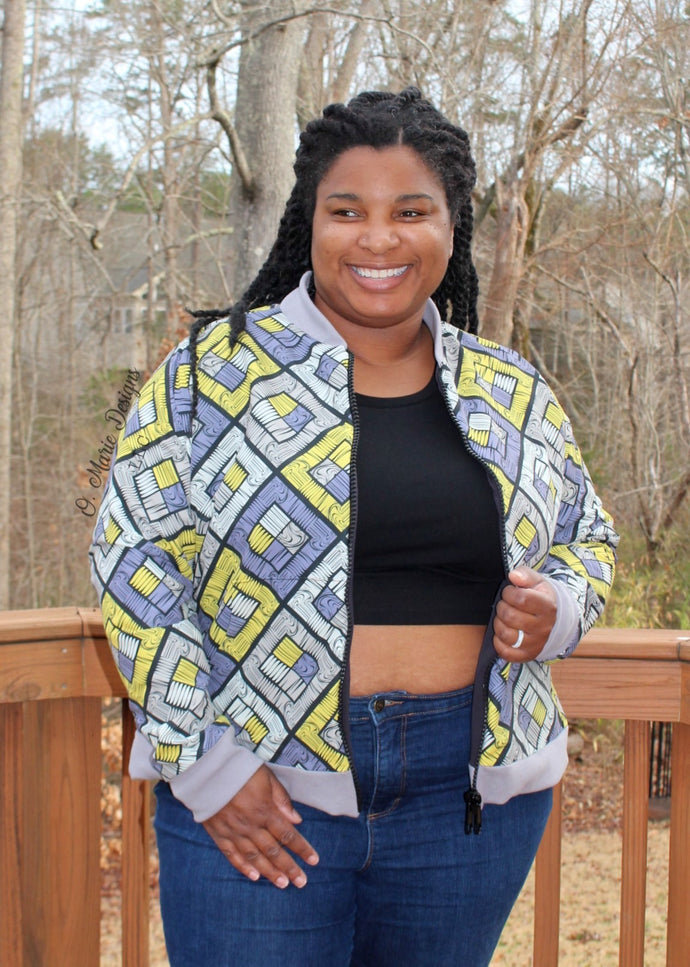 Image of beautiful Black woman in yellow and grey bomber jacket