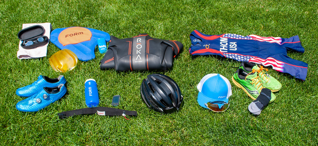 Various triathlon gear laid out on the grass including Form swim goggles, water bottle, swim cap, a helmet, and running shoes