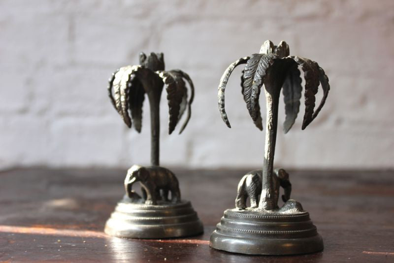 A Whimsical Pair of Victorian Bronzed Metal Candlesticks Each Formed as an Elephant Before a Palm Tree