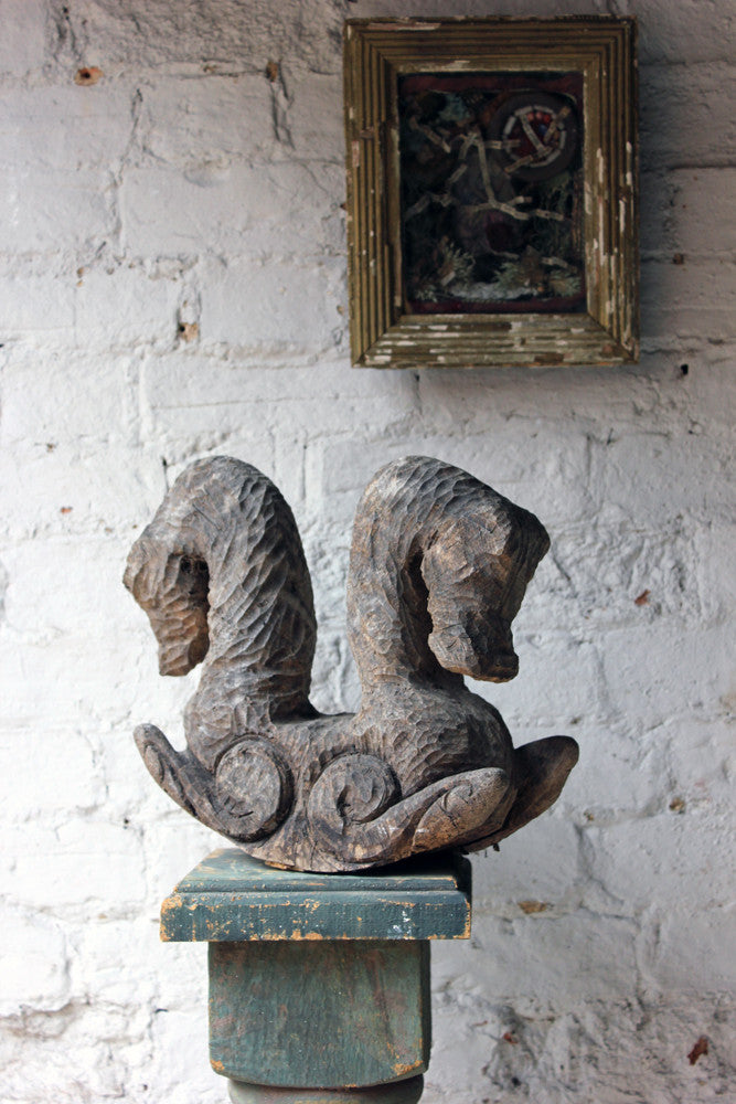 A decorative softwood chip carving of two seahorses doe