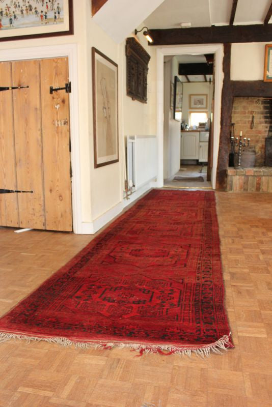 A Large Semi-Old Red Afghan Runner c.1950: 395cm x 95cm