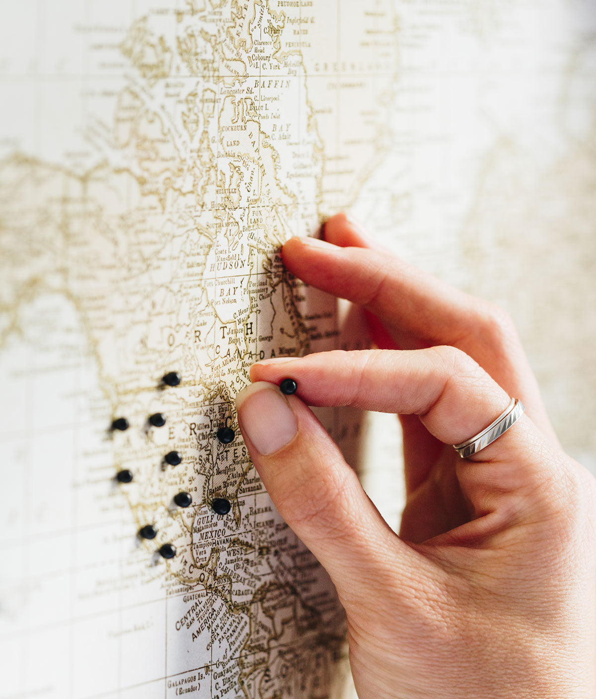 Woman's hand seen pinning locations on the anniversary push pin map